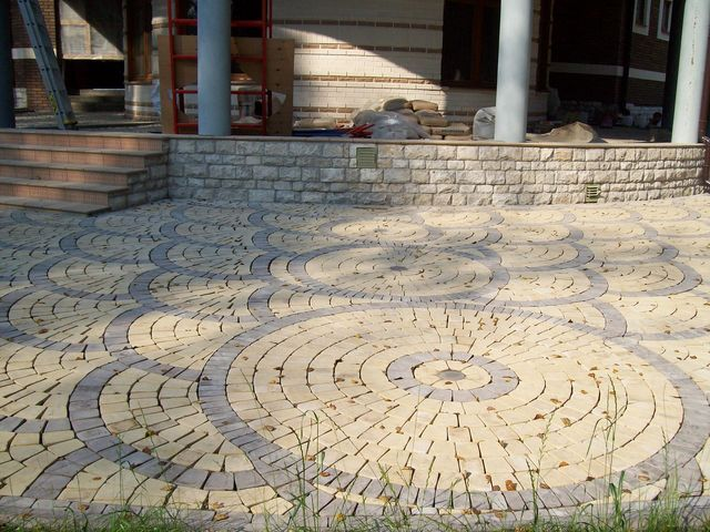 Тротуар викладений з бруківки.