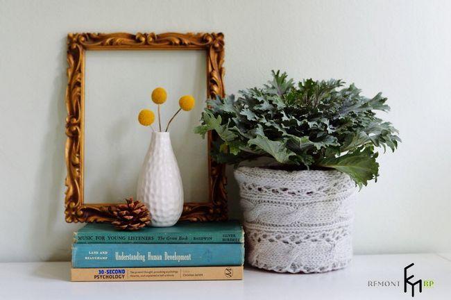 Вязаний горщик з квіткою поруч з білою вазою